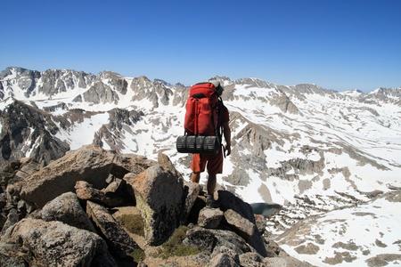 Achteraanzicht van een mannelijke backpacker neer te kijken op Piute Pass in de Sierra Nevada bergen vanaf Mount Emerson
