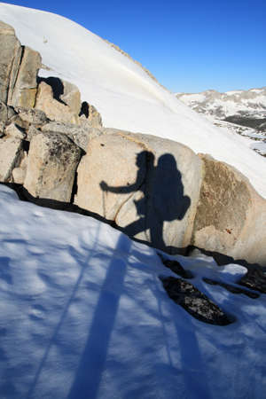 sierras: hiker with trekking poles shadow on a rock as a hiker or backcountry skier travels on snow with big backpack