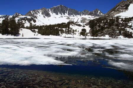 ice and snow in high mountain Long Lake with Mount Goode in the background in the Sierra Nevada of California photo