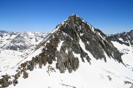 the 12652 ft tall Columbine Peak on a high snowpack early summer day from Isosceles peak in the Sierra Nevada mountains of California