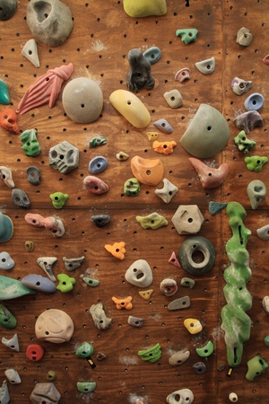 indoors: vertical image of homemade indoor artificial climbing wall covered with colored holds for rock climbing training
