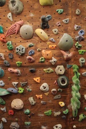 verticale afbeelding van zelfgemaakte indoor kunstmatige klimmuur bedekt met gekleurde houdt voor rotsklimmen training