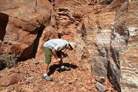 a man rockhounding at an outcrop with rock hammer Stock Photo