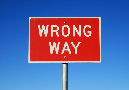 wrong way road sign on a blue sky background photo