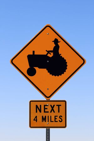 tractor warning: sign with a man on a tractor warning farm machinery for the next 4 miles with blue sky background Stock Photo