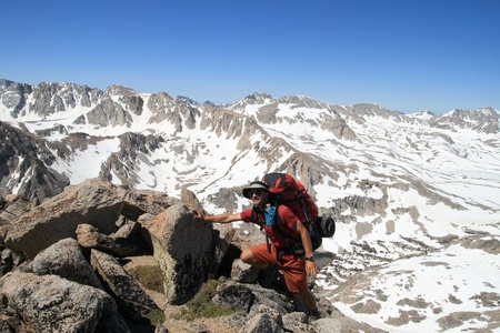 a male backpacker with large pack nears the summit in the Sierra Nevada in California Stock Photo - 10496256