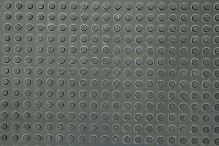 black rubber mat with round bumps in rows for background texture photo