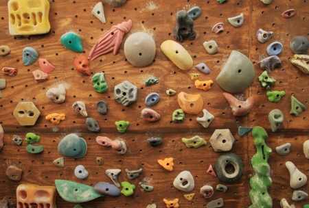 indoors: homemade artificial climbing wall covered with colored holds for rock climbing training Stock Photo