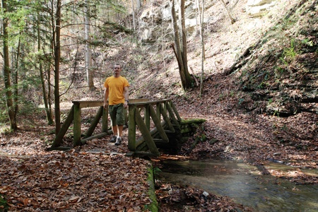 a man walking across a foot bridge in the woods in the fall Stock Photo - 11189444