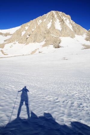 hiking man's shadow on snow and Mount Merriam in the Sierra Nevada mountains of California Stock Photo - 11454234