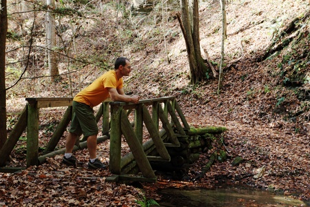 a man on a foot bridge in the woods in the fall Stock Photo - 11454278