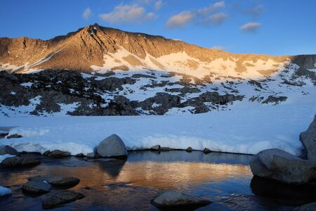 sierras: Mountain ridge in the Sierra Nevada mountains lit up by evening light and reflected in a stream Stock Photo