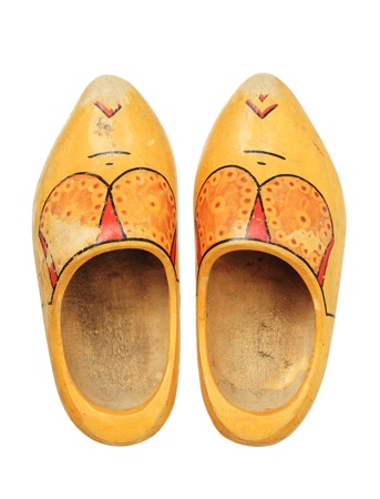 old worn used dutch wooden shoes on white background photo