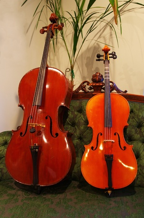 a full size cello and small cello sitting on a sofa photo