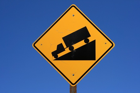 steep road sign with a truck driving down a steep downgrade in black and yellow on blue sky background