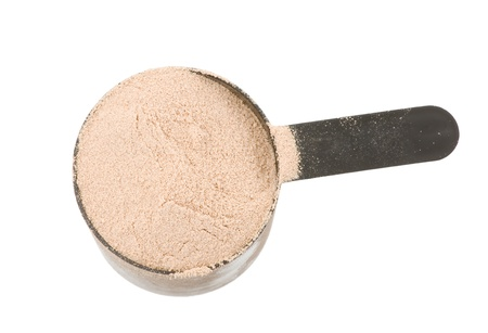 tight focus: chocolate flavor protein powder in a plastic scoop isolated on white background