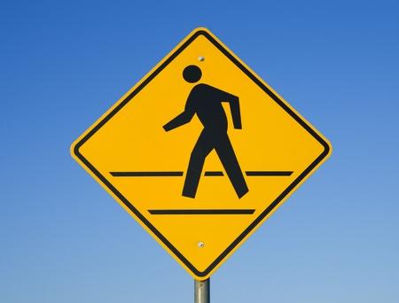 paso de peatones: señal de paso de peatones con un hombre caminando sobre amarillo con un fondo de cielo azul Foto de archivo