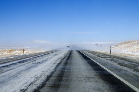 obscuring: blowing snow on a Wyoming interstate highway reduces visibility on a clear day obscuring other vehicles