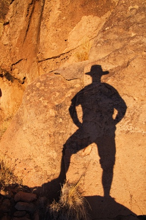 shadow: shadow of a man in a cowboy hat on a rock wall near sunset