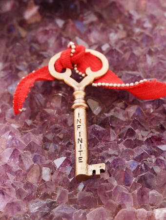 tight focus: infinite written on an antique brass key sitting on amethyst crystals
