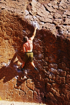 man with no shirt on rock climbing a boulder reaches for a hold Stock Photo