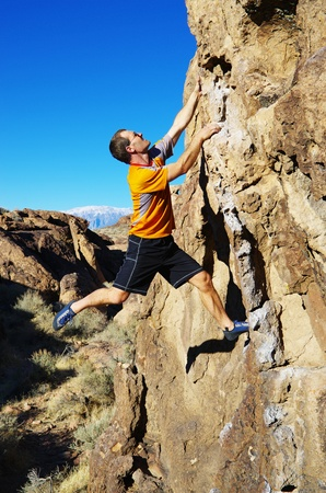 side view of man in an orange shirt rock climbing a boulder Stock Photo
