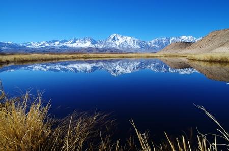 Sierra Mountain reflectie in een Oxbow van de Owens River met voorgrond grassen Stockfoto