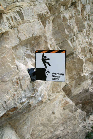 steep cliffs sign: steep cliffs warning sign bolted to a steep stone cliff face Stock Photo