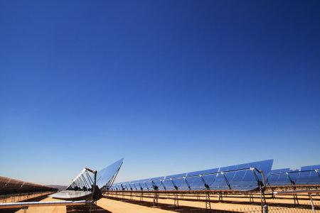 koncentrovaný: boční pohled na SEGS solární tepelné energie pouštní elektrárenských s parabolickými zrcadly, které se zaměřují na sluneční světlo s modrou oblohou kopií vesmíru Redakční