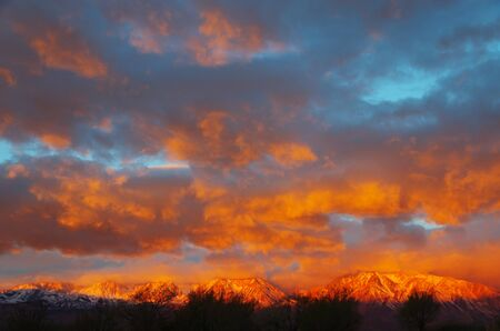 sunrise lights up the clouds and the eastern sierra mountains from Bishop California Stock Photo - 12712123
