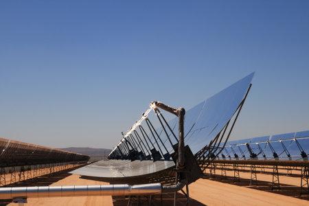 koncentrovaný: SEGS solární termální energie, poušť elektrárna s parabolickými zrcadly, které se zaměřují na sluneční světlo s modrou oblohou kopií vesmíru Redakční