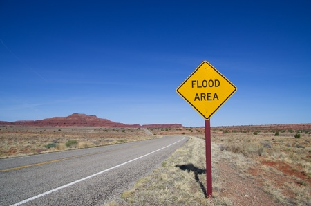 flood area: horizontal image of flood area sign and road in the Utah desert