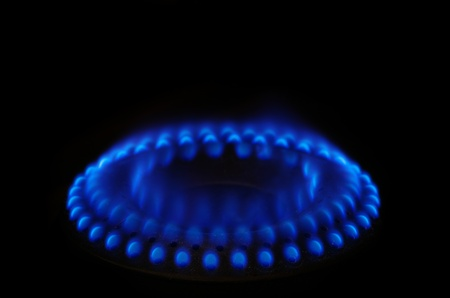 gas stove range burner with blue flame and dark background photo