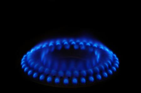 burner: gas stove range burner with blue flame and dark background Stock Photo