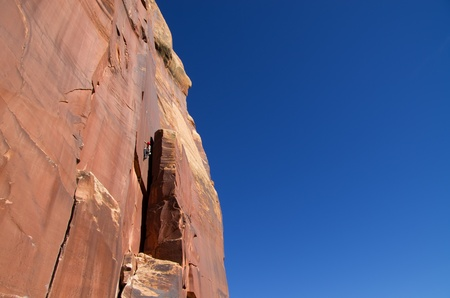 traditional climbing: distant image of a man crack rock climbing at Indian Creek Utah Stock Photo