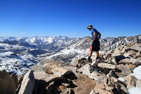 A man looking off over the side of Mount Rixford a mountain in the Sierra Nevada of California photo