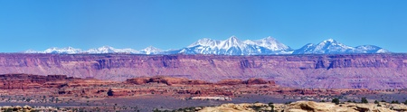 Sandstone cliffs and La Sal Mountains in a Canyonlands National Park panorama