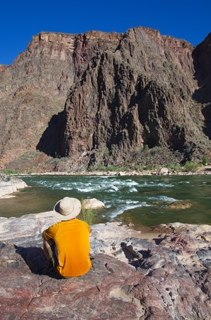 back view of a man sitting on a rock on the edge of the Colorado River at the bottom of the Grand Canyon photo