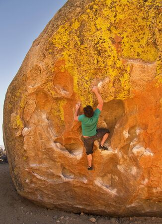 man rock climbing on a large boulder at the Buttermilk bouldering area Stock Photo - 13497921