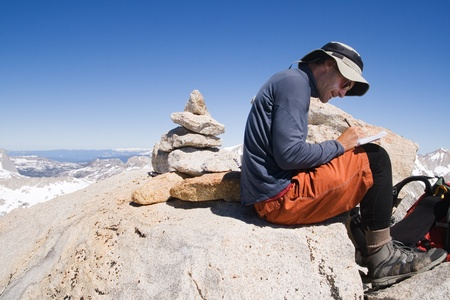 outdoorsman: a man signing the summit register on the peak of Mount Merriam
