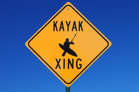 kayak crossing road sign that says kayak xing with blue sky background
