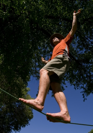 man balancing on a slackline pictured from below Stock Photo