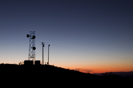 microwave antenna: silhouette of a microwave antenna tower against an evening sky