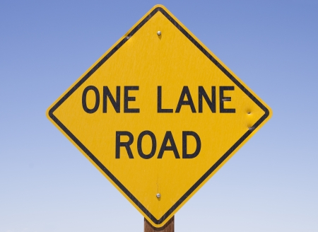 one lane street sign: yellow and black one lane road sign with blue sky background