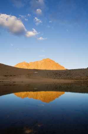high sierra: Mount Williamson reflection in a lake in the high Sierra with orange evening alpenglow lighting Stock Photo