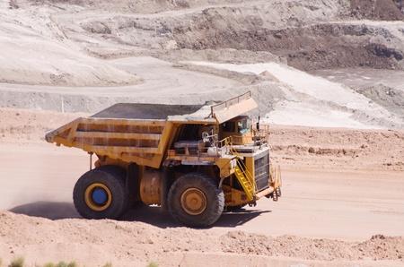 mining truck: distancia grande de color amarillo o conducir un camión volcado en una mina a cielo abierto Foto de archivo