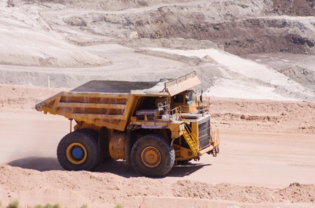 large yellow haul or dump truck driving at an open pit mine photo