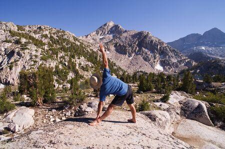 basin mountain: a man does the yoga triangle pose or trikasana in nature Stock Photo