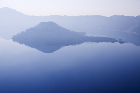 Wizard Island in Crater Lake on a hazy day with reflections and copy space photo