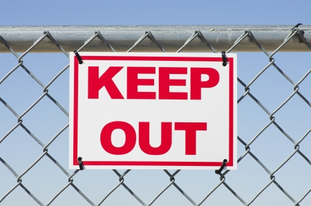 red and white keep out sign on a chain link fence photo
